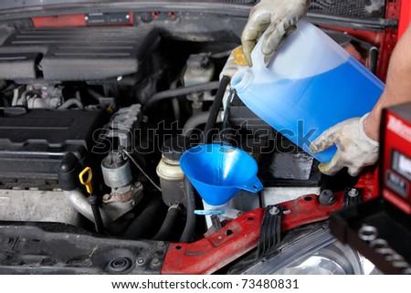 Windscreen washer. Mechanic working in auto repair shop. - stock photo