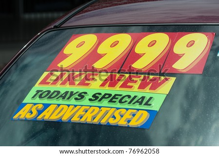 windshield price sticker on a used car lot for sale - stock photo