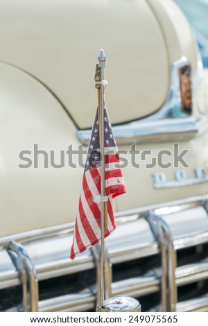 WINDSOR, BERKSHIRE, UK- August 4, 2013: An American flag mounted on the hood of a cream Dodge Coronet Classic car on show at Windsor Farm Shop International Classic Car Show in August 2013 - stock photo