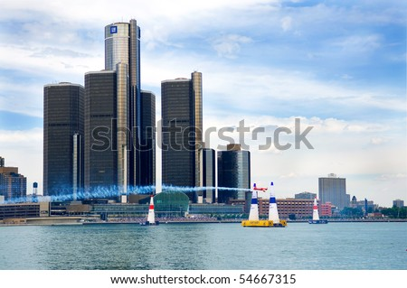WINDSOR, ONT - JUNE 5 - The Red Bull airplane races by the Diamler Chrysler, and CIBC buildings at the Red Bull Air Races June 5, 2010 on the Detroit River in Windsor, Ontario - stock photo