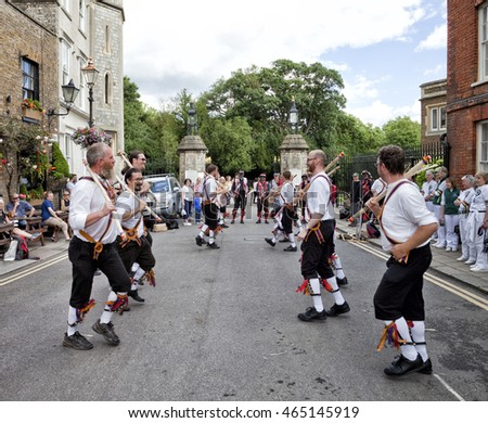 WINDSOR,UNITED KINGDOM - JUNE 25, 2016: Morris dancers in Windsor, England. Traditional dancers with people watching on busy city street.