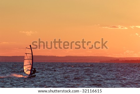 Windsurfer go fast on lake beautiful colors at sundown - stock photo