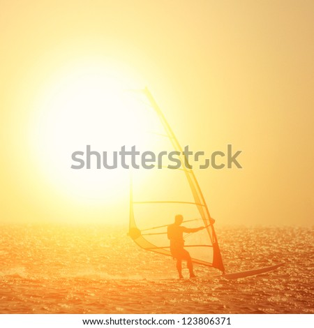 Windsurfer in the sea during sunset - stock photo