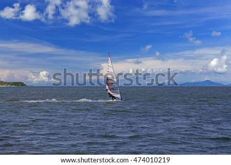 Windsurfer in wetsuit sailing in the ocean, blue cloudy sky