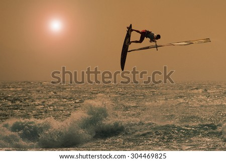 windsurfer jumping in a sunset sky - stock photo