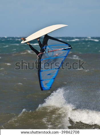 Windsurfer jumping on a wave with the board on the top, upside - down. Extreme action sports. - stock photo