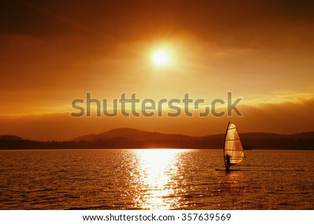 Windsurfer leans back into breeze Shot with gentle filter. Strong sun makes reflections in mirror of water level. - stock photo