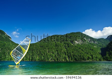 Windsurfer on mountain lake. Copyspace on blue sky. - stock photo