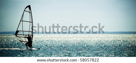 windsurfer panorama silhouette against a sparking blue sea - stock photo