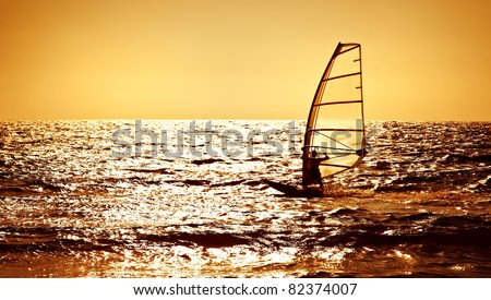 Windsurfer silhouette over sea sunset, panoramic beach landscape, summertime fun, sport, activities, vacation and travel concept - stock photo