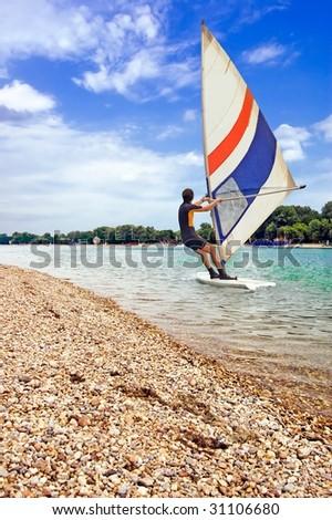 Windsurfer surfing on a beautiful lake near coast. - stock photo
