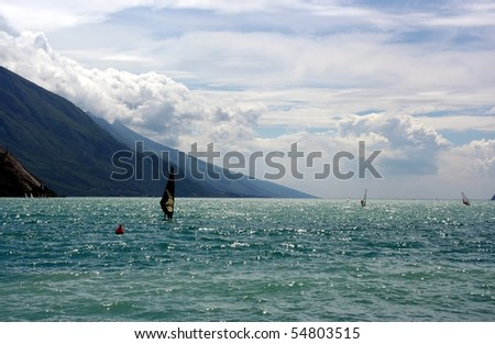 Windsurfer with black sail on a lake with mountains as a background - stock photo
