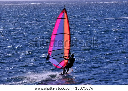 windsurfer with bright colored sail on caribbean blue water - stock photo