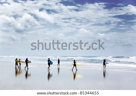 windsurfers heading out to sea on a stormy day - stock photo