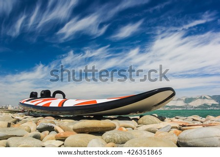 Windsurfing board on the beach on the background of cloudy sky - stock photo