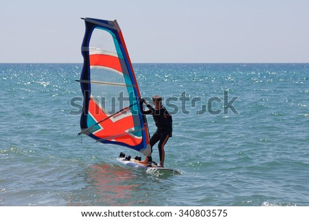 Windsurfing in a calm day with clear blue sky and Mediterranean Sea