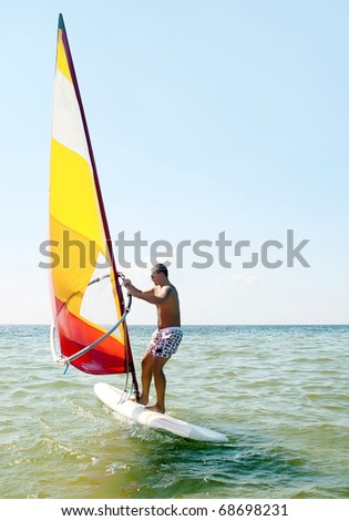 Windsurfing man in sea lagoon - stock photo
