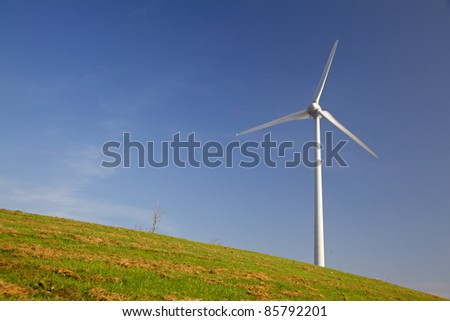 Windturbine in a grass field with a clear blue sky