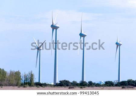 windturbines conducting electricty on an open field - stock photo