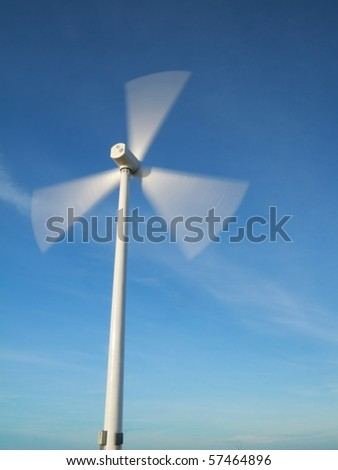 windy day with motion blade of modern wind turbine. - stock photo