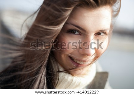 Windy portrait of attractive young girl with a cheerful toothy smile. The model showing friendly facial expression and her hair looks beautiful - stock photo