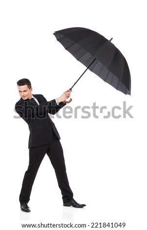 Windy weather. Elegance man holding an open umbrella. Full length studio shot isolated on white. - stock photo
