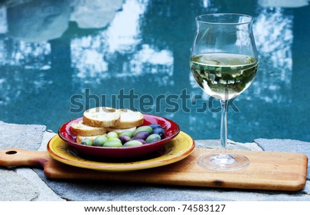 Wine and appetizers poolside - stock photo