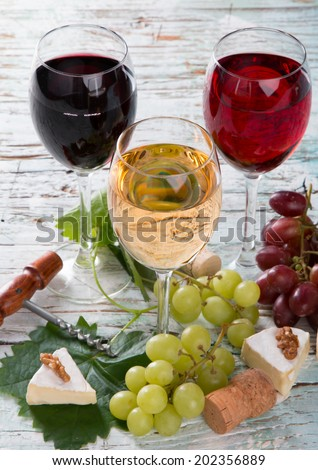 Wine and cheese on wooden table with fresh grapes  - stock photo