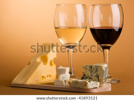 Wine and cheese over brown background still-life photo - stock photo