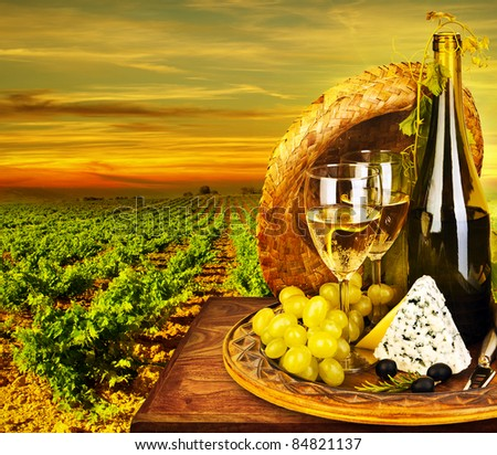 Wine and cheese romantic dinner outdoor, table for two with vineyard view, fresh grapes and wineglass at restaurant, warm autumn sunset, grape field landscape at harvest, food still life - stock photo