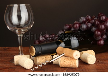 Wine and corks on wooden table on brown background - stock photo