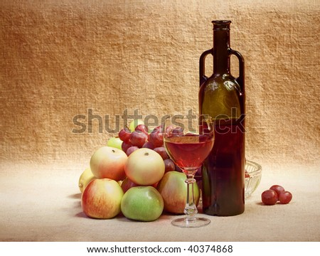 Wine and fruit against a brown sacking - still life - stock photo