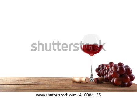 Wine and grape on wooden table against light background - stock photo