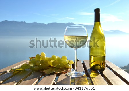 Wine and grapes against Geneva lake, Switzerland - stock photo
