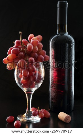 wine and grapes on a table and a dark background - stock photo