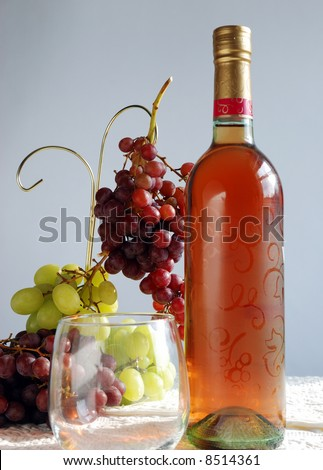 Wine and grapes still life - bottle of white zinfandel with red and green grapes in the frame - stock photo