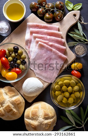 Wine appetizer set. Antipasti Platter of baked ham, red and yellow cherry tomatoes, black zebra cherry tomato, black and green olives, the leaves of the olive tree, salt and pepper, bread turtle. - stock photo