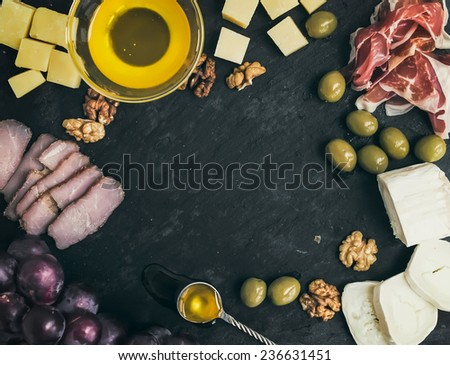 Wine appetizer set: cheese and meat selection with grapes, honey, olives and walnuts on black stone background with a copy space in the center. Top view - stock photo