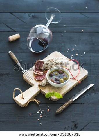 Wine appetizer set. Glass of red wine, French sausage and olives on black wooden backdrop, selective focus - stock photo