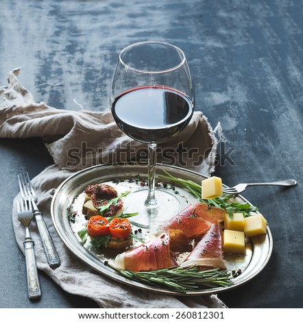 Wine appetizer set. Glass of red wine, vintage dinnerware, brushetta with cherry, dried tomatoes, arugula, parmesan, smoked meat on silver tray over rustic grunge surface. Closeup - stock photo