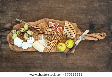 Wine appetizers set: cheese selection, honey, grapes, almonds, walnuts, bread sticks, figs on olive wood serving board over rustic background , top view - stock photo