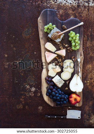 Wine appetizers set: French cheese selection, honeycomb, grapes, peach and walnuts on rustic wooden board over dark grunge metal background. Top view, copy space - stock photo