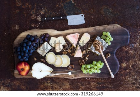 Wine appetizers set: French cheese selection, honeycomb, grapes, peach and walnuts on rustic wooden board over dark grunge metal background. Top view, - stock photo