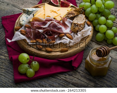 Wine appetizers set: meat and cheese selection, grapes, nuts on a dark rustic wooden background - stock photo