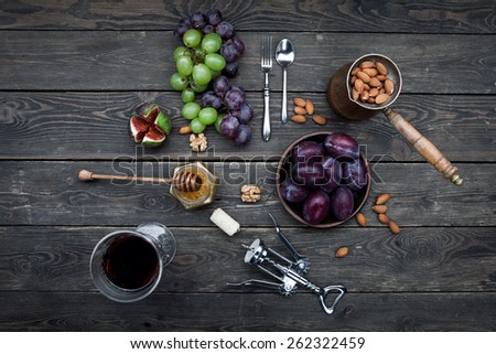 Wine appetizers set with fruits: grapes, nuts, plums and honey on a dark rustic wooden background - stock photo