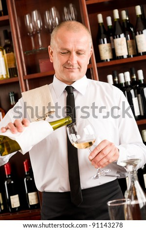 Wine bar happy waiter pour white wine in glass restaurant - stock photo