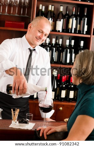 Wine bar professional waiter serve glass senior woman smiling - stock photo