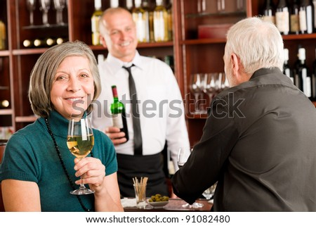 Wine bar senior couple enjoy drink smiling barman discussing - stock photo