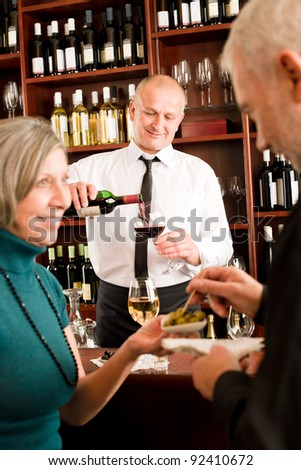 Wine bar senior couple enjoy drink smiling barman pour glass - stock photo