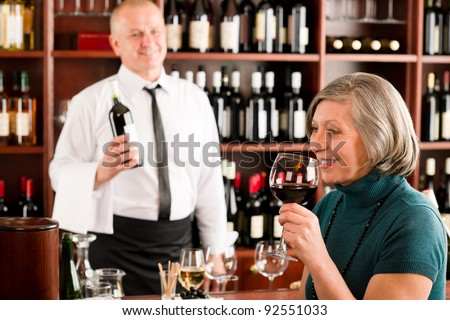 Wine bar senior woman enjoy wine glass in front of bartender - stock photo